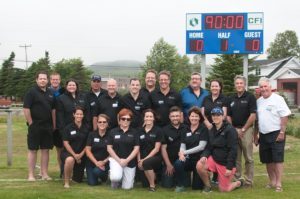 CFI staff and St. Lawrence Soccer Association members celebrate the unveiling of the new scoreboard donated by CFI.